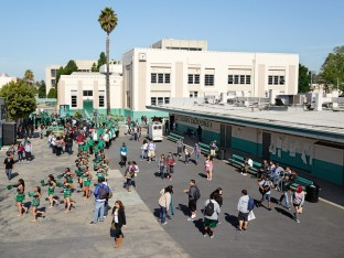 Inglewood High School, Inglewood, California. The cheerleaders, in green, are on their way to the sports field, followed by the school band. Many of the school's recent notable alumni are professional athletes. In the US, often more tax dollars are spent on high school athletes than on high school math students.